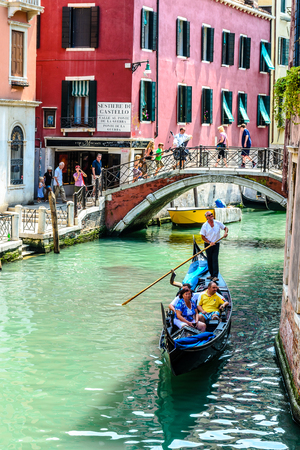 11 July 2013: Beautiful view on canal with gondola, gandolier,  colorful houses in Venice, Italy.