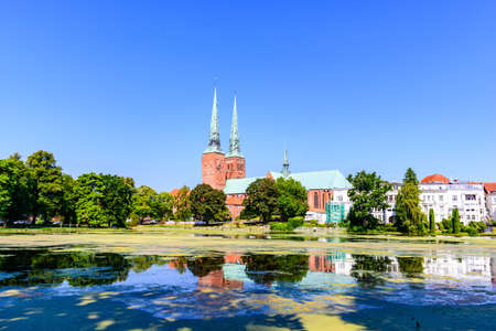 Cathedral church (Dom) with a lake, blue sky in Lubeck (Lübeck), Schleswig-Holstein, Germany Banco de Imagens