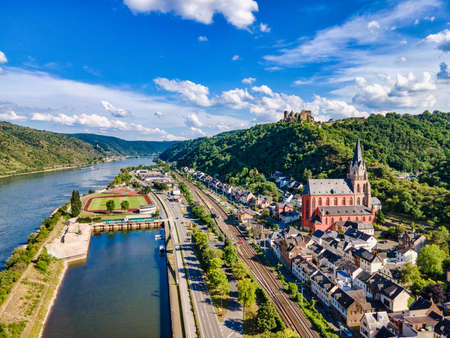 Aerial view on Oberwesel am Rhein. Small town on the upper middle Rhine River, Middle Rhine. Beautiful panoramic postcard with blue sky, clouds. Rhineland-Palatinate (Rhineland-Palatinate), Germany. UNESCO