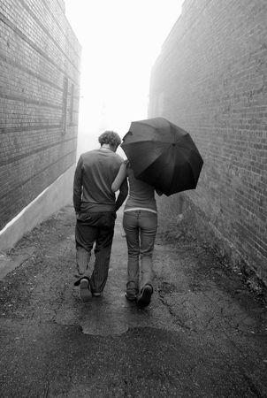 walking in the rain: couple walking in alley on a rainy day with umbrella