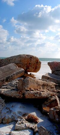 Rocky ruins of old pier on a beach photo