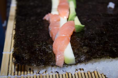 maki sushi: Making delicious maki sushi with salmon, avocado and cucumber.