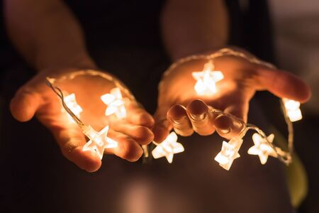 light to dark: Hands holding shiny Christmas lights with star shapes