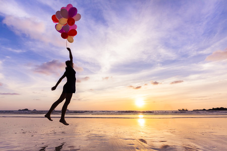 Woman in a happy dream flying in the sky lifted by helium balloons