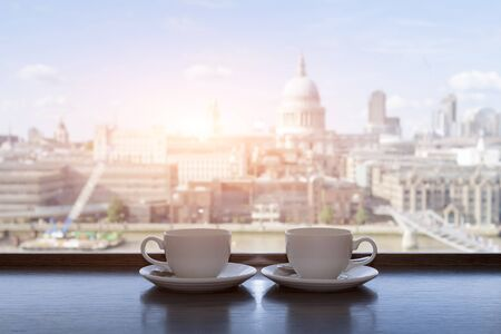 city of sunrise: Two cups of coffee with panoramic view of a city in background