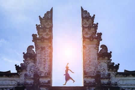 Vrouwenreiziger die met energie en vitaliteit in de poort van een tempel, Bali, Indonesië springen Stockfoto