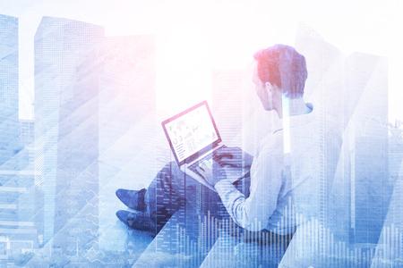 주식 시장 투자 대시 보드와 밝은 추상적 인 배경으로 사용할 수있는 금융 지구 건물 랩톱 컴퓨터를 사용하는 사업가의 이중 노출 스톡 콘텐츠