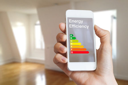 Energy efficiency rating on smartphone app by woman real estate agent and home interior in background Imagens