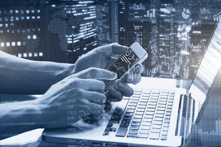Doppelbelichtung von abstrakten finanziellen Graphen, Business Person im Büro unter Verwendung Smartphone und Laptop-Computer mit Börse Armaturenbrett und Gebäude