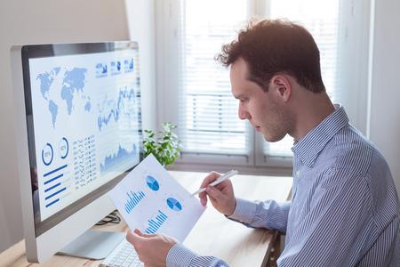 Inwestor analizujący sprawozdania finansowe i kluczowe wskaźniki efektywności (KPI) rynku akcji na ekranie komputera z analityką biznesową (BI) i wykresami w biurze