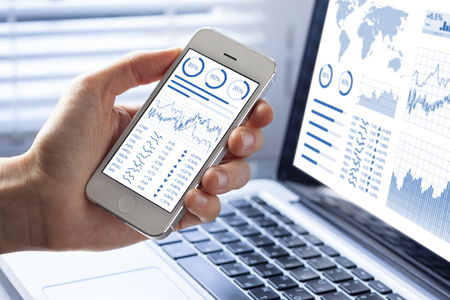 Investor analyzing stock market investments with financial dashboard, business intelligence (BI), and key performance indicators (KPI) on smartphone and computer screens Stockfoto