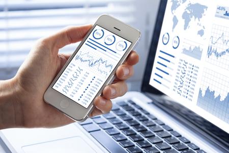 Investitore che analizza gli investimenti del mercato azionario con cruscotto finanziario, business intelligence (BI) e indicatori chiave di performance (KPI) sugli smartphone e sul computer Archivio Fotografico
