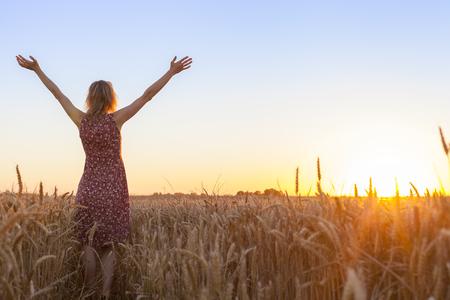 Heureuse femme positive pleine de vitalité levant les mains et face au soleil dans un champ de blé au lever du soleil