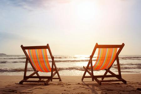 Deux chaises longues sur la plage avec soleil et vagues
