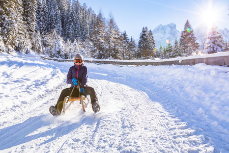 Cheerful girl riding a sled downhill on a snow covered sledge trail in a white sunny winter mountain landscape Stockfoto