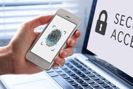 指紋バイオメトリクス セキュリティのため携帯電話のバック グラウンドでコンピューターのスキャンを使用している人 写真素材
