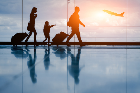 Silhouette of young family and airplane at airport