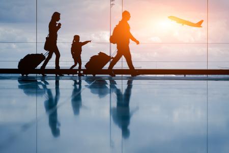 gente aeropuerto: Silueta de la familia joven y el avión en el aeropuerto