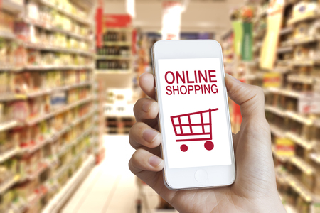 Online shopping application on mobile phone screen with grocery store in the background