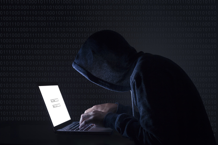 initiating: Hacker with laptop initiating cyber attack