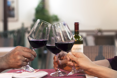 syrah: Group of friend clinking glasses of wine in a restaurant Stock Photo