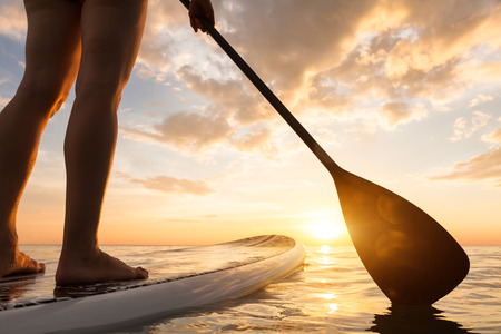 Stand up paddle boarding on a quiet sea with warm summer sunset colors, close-up of legs 스톡 콘텐츠