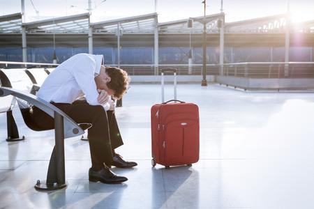 Deprimido viajero espera en el aeropuerto después de los vuelos retrasos y cancelaciones