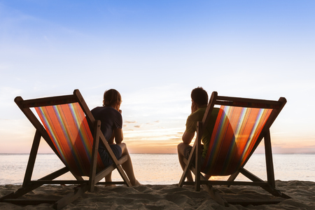 Couple sitting in deckchairs on paradise beach and thinking about perfect life Stock Photo