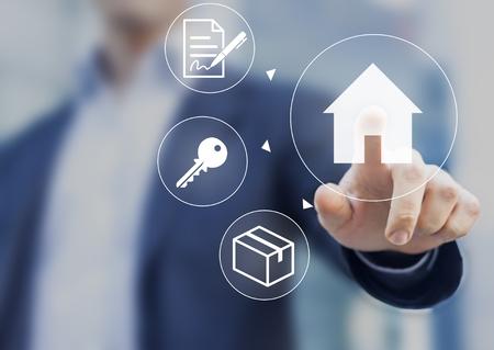 住宅ローンの契約、キー ボックスとスクリーンの家ボタンを押す手