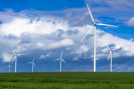 generate: Windturbines in a green field generate sustainable energy Stock Photo