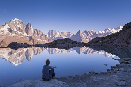 Female traveler looking the Alps mountain range at sunset with beautiful reflection in a lake, near Chamonix and the White Mount