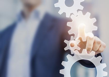 Automazione dei processi aziendali e concetto di miglioramento del flusso di lavoro rappresentato da un uomo d'affari che tocca una ruota dentata collegata ad altri ingranaggi
