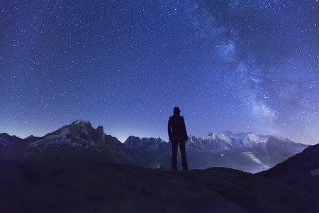 alone person: Person watching the stars and the Milky Way in the night sky above the Alps mountain range and the White Mount near Chamonix