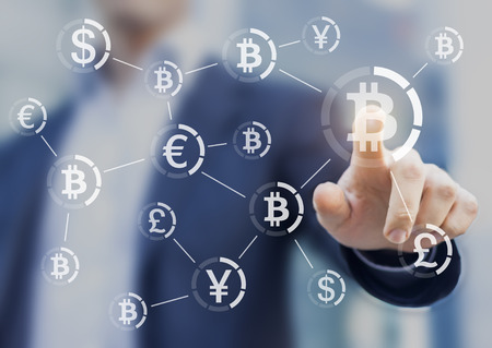 Bitcoin button on virtual interface displaying the payment system, businessman touching the currency symbol