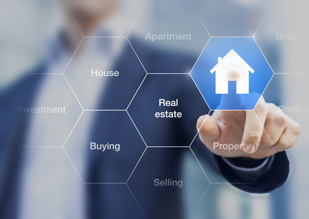 Immobilienmakler, der einen Knopf mit einem Symbol des Hauses auf einem transparenten Schirm betätigt Standard-Bild