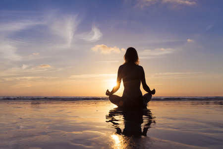 Young woman meditating and relaxing on the beach with yoga, beautiful view of sunrise