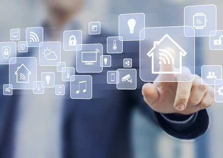 Internet of things (IOT) concept related to smart home automation and connected objects with a person touching a virtual interface Stockfoto