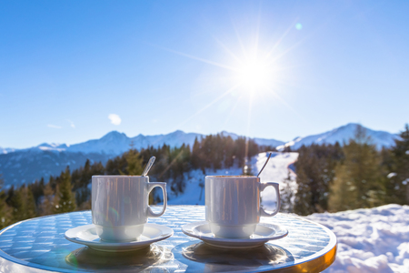 Two hot chocolate mugs on the terrace of an altitude restaurant in the mountain ski resort with beautiful sunny white winter background Stock Photo