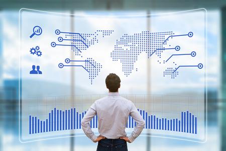 Worldwide Business-Konzept mit einer Person, die eine futuristische Head-up-Display (HUD) mit einer Weltkarte und Grafik-Anzeige über den internationalen Vertrieb zu analysieren