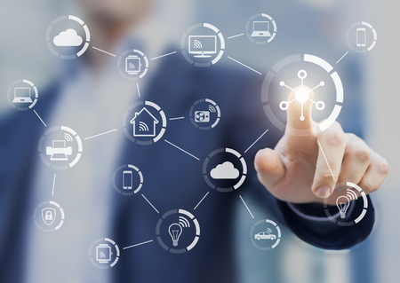 Internet of things (IOT) concept with a network of connected objects exchanging data with wireless connection, person touching virtual screen, smart home