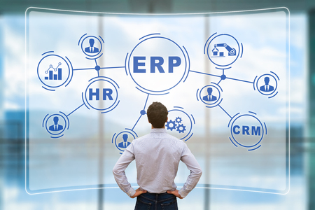 IT manager analyzing the architecture of ERP (Enterprise Resource Planning) system on virtual AR screen with connections between business intelligence (BI), production, HR and CRM modules