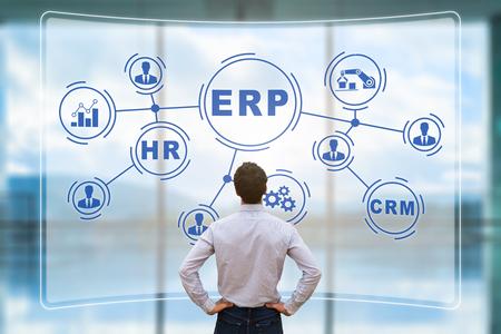 Responsable informatique analysant l'architecture du système ERP (Enterprise Resource Planning) sur écran AR virtuel avec des connexions entre les modules BI (Business Intelligence), production, HR et CRM