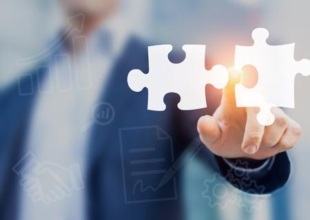 Połączenia i koncepcja przejęcia z konsultantem dotykając ikony elementów układanki reprezentujących połączenie dwóch spółek lub wspólne przedsięwzięcie, partnerstwo