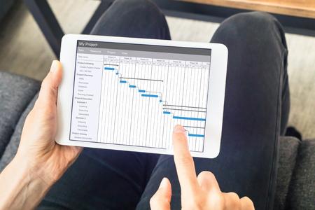 Projektmanager, der mit Gantt Diagramm mit Planungssoftware auf digitalem Tablettencomputer arbeitet, um den Zeitplan und die Fristen zu aktualisieren
