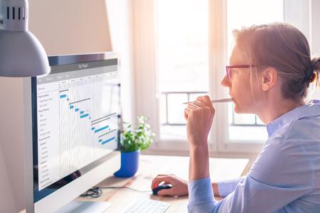Gestor de proyecto femenino que utiliza el diagrama de Gantt para organizar las tareas y actualizar la planificación en la pantalla del ordenador con el software