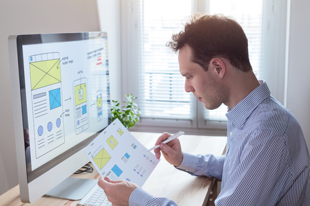 Website UI/UX front end designer reading client specification document and sketching wireframe layout design for responsive web content