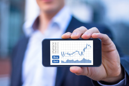 Trader showing smartphone screen with trading interface dashboard with candlestick chart, quotes and buy sell buttons, stock exchange and fintech concept