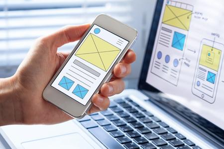 Mobile responsive website development with UI/UX front end designer previewing wireframe sketch layout design mockup on smartphone screen Standard-Bild
