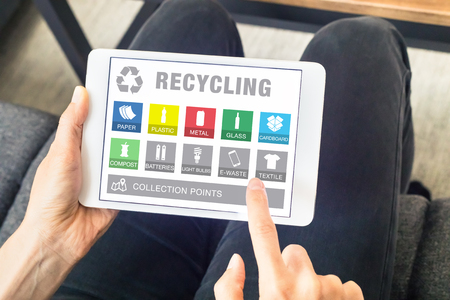 e waste: Person using digital tablet computer with app website for sorting recyclable material waste (icons of paper, plastic, metal can, glass bottle, e-waste) and searching collection points, recycling concept