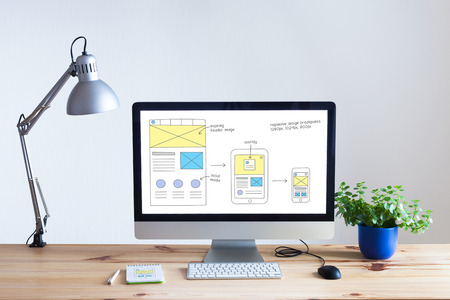 Responsive web design development technology concept with desktop computer in modern bright office and website wireframe sketch layout on screen, nobody 스톡 콘텐츠